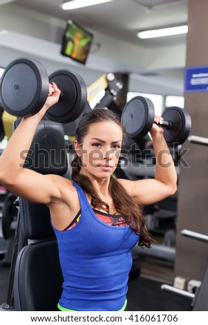 Young Fitness Woman holding a hand weight