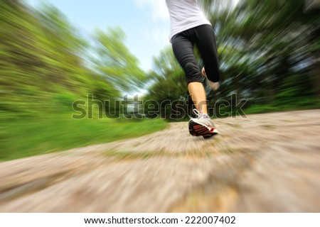 young fitness woman legs running at forest stone trail  - stock photo