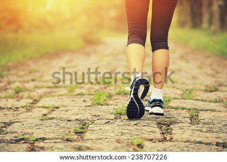 young fitness woman legs walking at forest trail  - stock photo