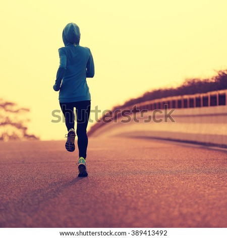 young fitness woman runner athlete running on sunrise road