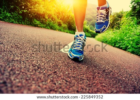 young fitness woman runner legs running at forest trail  - stock photo