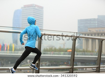 young fitness woman runner running on city