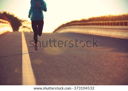 young fitness woman runner running on sunrise road - stock photo
