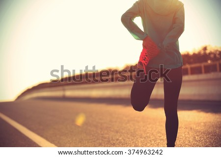 young fitness woman runner stretching legs before run - stock photo