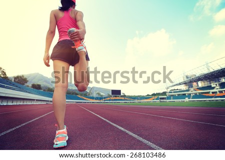 young fitness woman runner warm up before running on track - stock photo