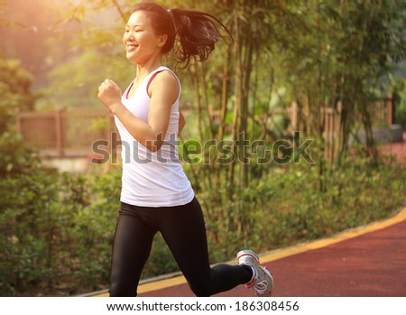young fitness woman running cross country   - stock photo