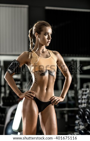 young fitness woman tired in gym and listen music with headset, vertical photo - stock photo