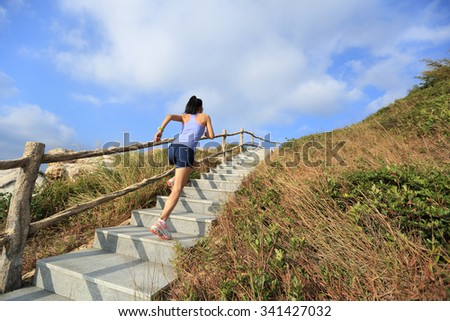 young fitness woman trail runner running up on mountain stairs - stock photo