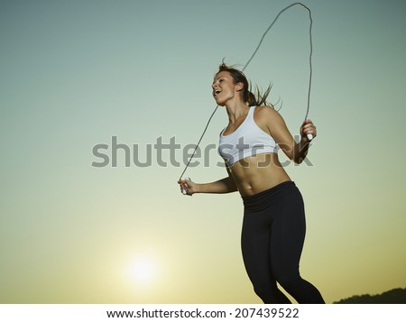 Young fitness woman used a skipping rope, sun and sky on background, copy space - stock photo