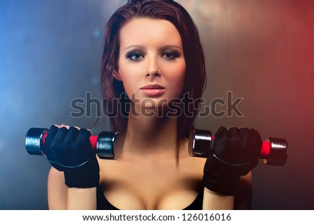 Young fitness woman with dumbbells portrait.