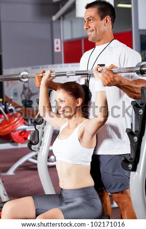 young fitness woman with personal trainer in gym - stock photo