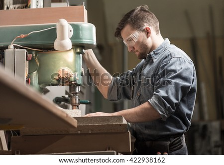 Young focus man working in a carpentry with big electronic machine