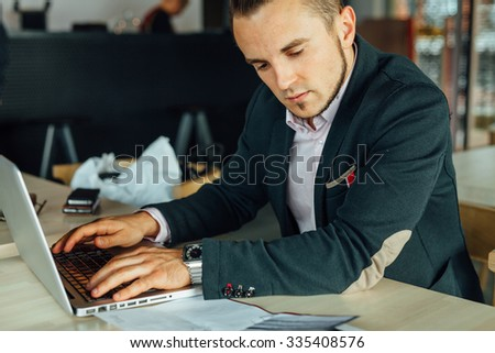 Young focused businessman sitting in cafe with laptop and analyzing documents. Indoor photo