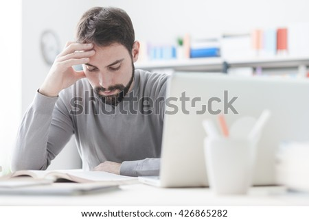 Young focused smart man in the office studying and reading a book, shelves on background
