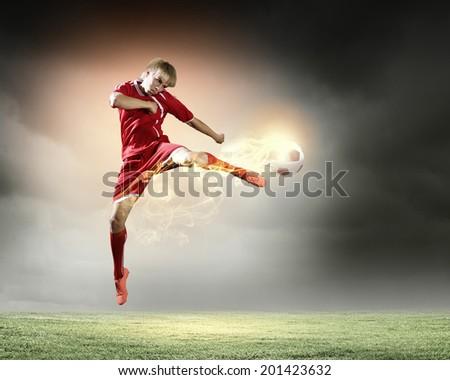 Young football player on stadium kicking ball - stock photo