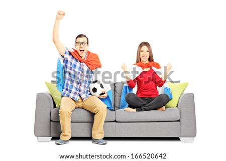 Young football supporters sitting on a modern sofa, isolated on white background - stock photo
