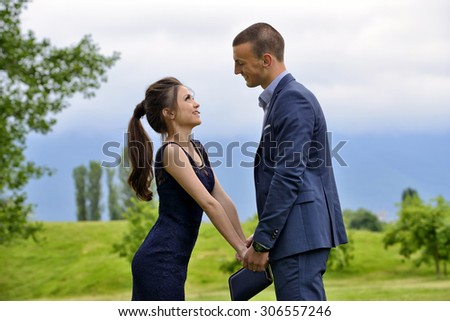 Young formally dressed couple looking lovingly at each other - stock photo