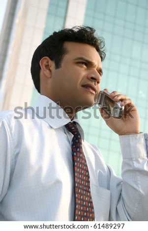 young formally dressed executive busy talking business on the phone - stock photo