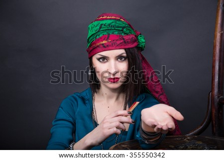 Young fortune teller with a penetrating gaze stretches out his hand forward. Predicting the future. - stock photo