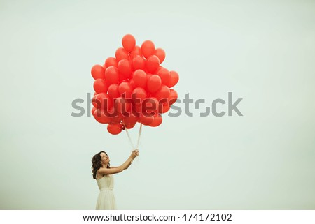 Many Beautiful Balloons In The Sky : young fragile woman let many red balloons in the sky