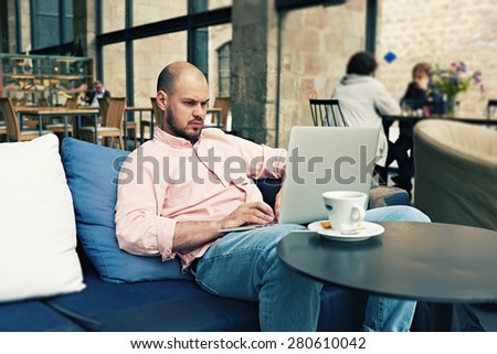 Young freelancer sitting at sofa while thoughtfully work on his notebook, successful businessman having coffee break while read some news on laptop computer with cup of cafe or tea on the table - stock photo