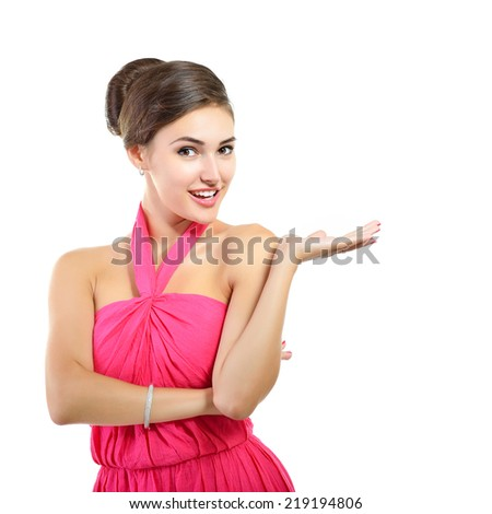 Young fresh attractive woman in pink dress pointing something with her hand, over white