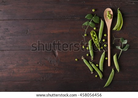 young fresh pods of green peas on wooden table