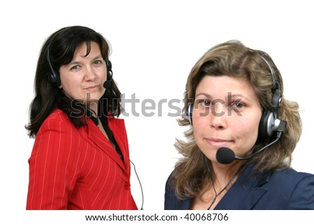 Young friendly brunette woman with headset smiling during conversation (focus on the back girl)