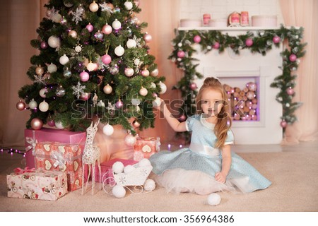 Young friendly girl smile and seat near gift box and dressed Christmas tree. New Year celebration. - stock photo