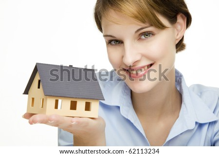 young friendly smiling businesswoman presenting a model house - stock photo