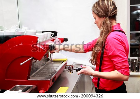 Young friendly waitress making cappuccino at coffee machine in the cafe