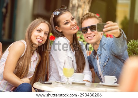 young friends  at cafe taking selfie in a cafe - stock photo