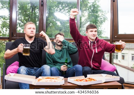 Young friends cheering and drinking alcohol while watching soccer match at home - stock photo