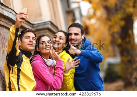 Young friends doing selfie after jogging.They standing against the wall.