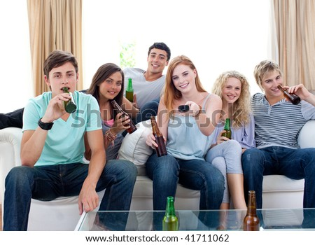 Young friends drinking beer and watching tv at home - stock photo