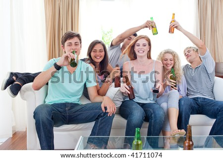 Young friends drinking beer at home - stock photo