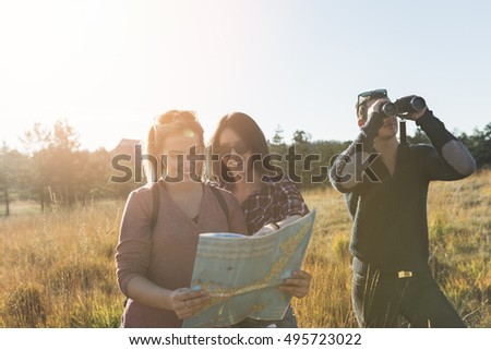 Young friends enjoying outdoor. Two girls standing in deep grass, smiling and looking at map to find best route while young man looking through binoculars.