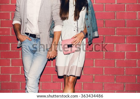 Young friends funny guys active people have fun together woman and man, girl and guy summer urban casual style. Pink brick wall, spring  outfit. - stock photo