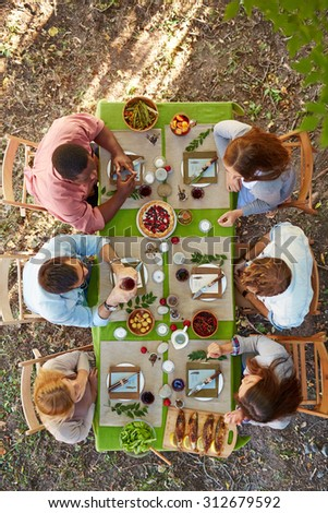 Young friends having dinner on Thanksgiving Day outdoors - stock photo