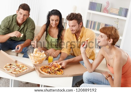 Young friends having party at home, eating pizza and chips, smiling. - stock photo