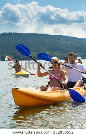 Young friends kayaking in summertime on lake holiday - stock photo
