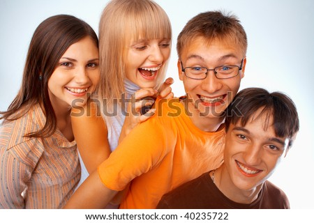 Young friends laughing together standing in a row - stock photo