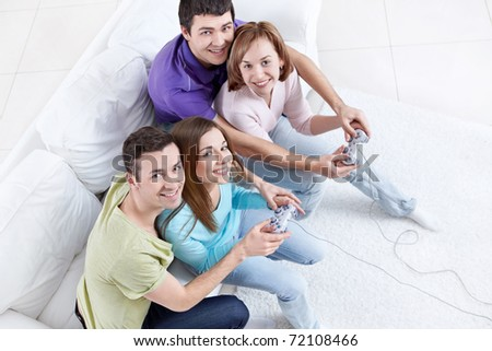 Young friends playing video games - stock photo