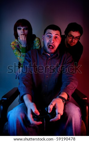 Young friends playing video games in front of tv or computer - stock photo