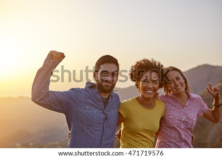 Young friends posing for a celebrating picture in the late afternoon sunshine on a mountain them while wearing casual clothing
