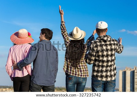 Young Friends Staying and Expressing Positive Emotions Four People Men and Women Together on Blue Sky Background Casual Jeans Style Dress Hands Gesturing Smiling Laughing - stock photo