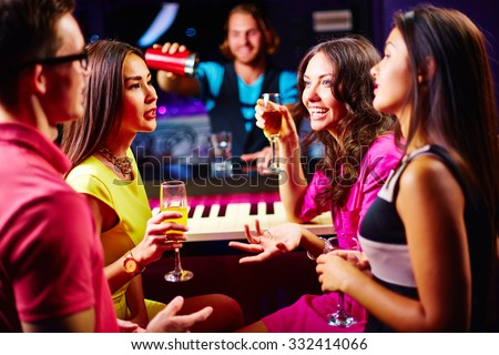 Young friends talking at party while drinking champagne - stock photo