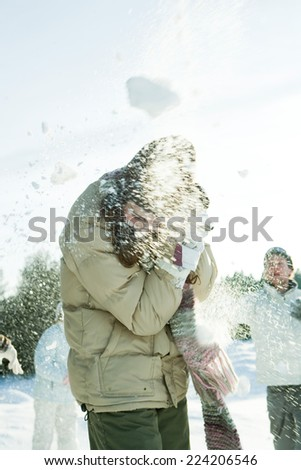 Young friends throwing snowballs at each other, blurred motion - stock photo
