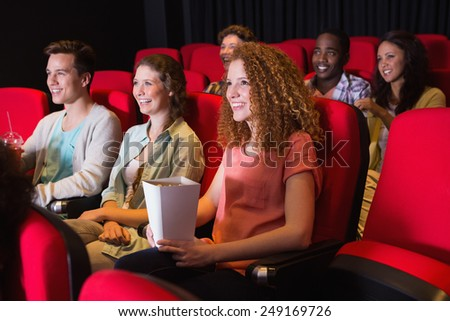 Young friends watching a film at the cinema