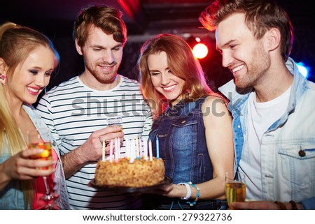 Young friends with champagne and cake with candles having birthday party